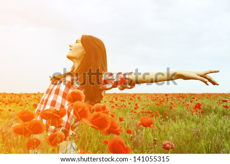 Young beautiful woman walking and dancing through a poppy field, summer outdoor. Toned, noise added. - stock photo