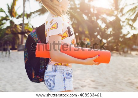 young beautiful woman walking on beach holding yoga mat, hipster sport swag style, denim shorts, t-shirt, backpack, sunny, summer weekend, cheerful, hand close-up - stock photo