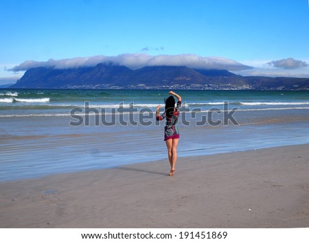 Young beautiful woman walking on the Sunrise beach in Cape Town. Muizenberg. Atlantic ocean. South Africa. Blowing long hair. Fashion shooting. Oriental style. Boho-chic. - stock photo