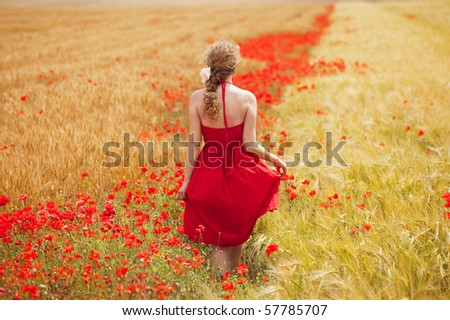 young beautiful woman walking through a  poppy field in summer - stock photo
