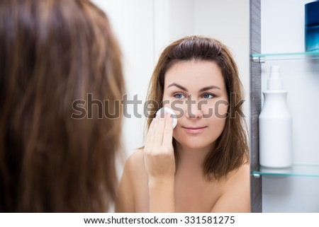 young beautiful woman washing her face with lotion in bathroom - stock photo