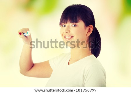 Young beautiful woman washing her teeth with blue brush - stock photo
