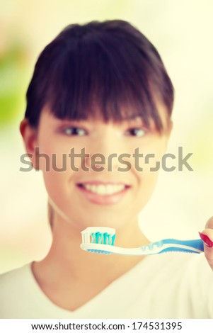 Young beautiful woman washing her teeth with blue brush - focus on brush - stock photo