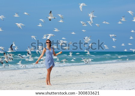 Young beautiful woman watching the seagulls flying - flock of birds, Siesta Key beach, Florida - stock photo