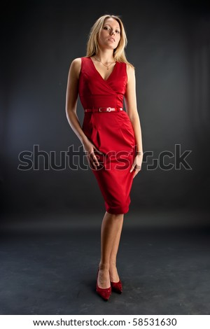 Young beautiful woman wearing a red dress on the dark background in the studio