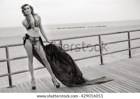 Young beautiful woman wearing bikini and fluttering cover up posing sexy on the boardwalk at the beach. - stock photo