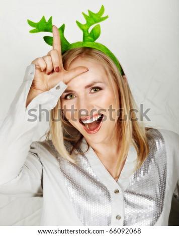 young beautiful woman wearing reindeer horns making fun. - stock photo