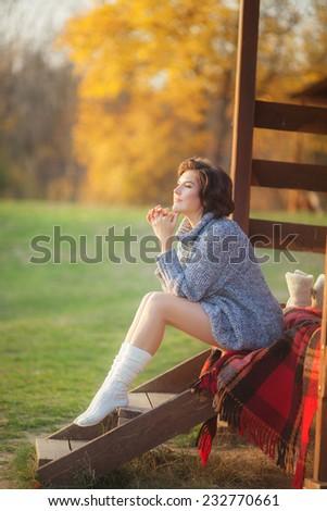 Young beautiful woman wearing warm knit clothes. Outdoors in sunlight. Model fashion shooting. Autumn, winter season. Leggings. Gaiters. Golfs.   - stock photo
