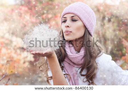 Young beautiful woman wearing winter clothing in the snow