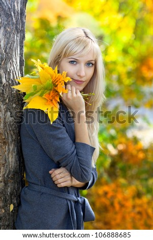Young beautiful woman with a bouquet of autumn leaves - stock photo