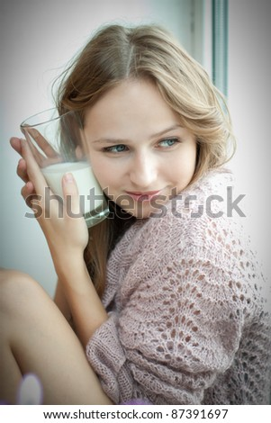 Young beautiful woman with a glass of fresh milk.