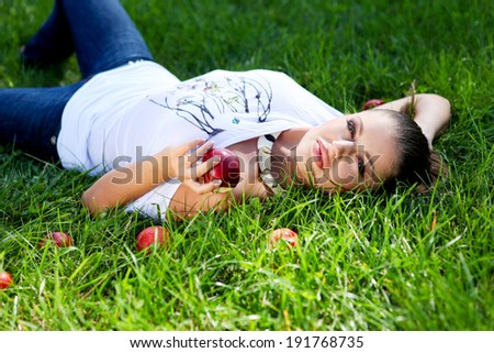 Young beautiful woman with apple on the green grass - stock photo