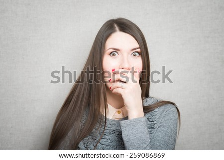 Young beautiful woman with astonished expression - stock photo