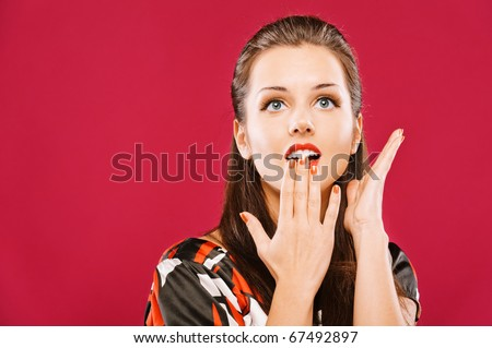 Young beautiful woman with astonishment covers mouth with palm, on red background.