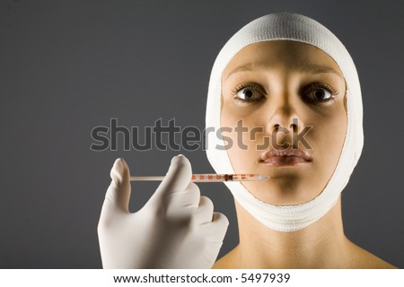 Young, beautiful woman with bandage on head. Somebody is injecting something in her's lips. Front view, Gray background
