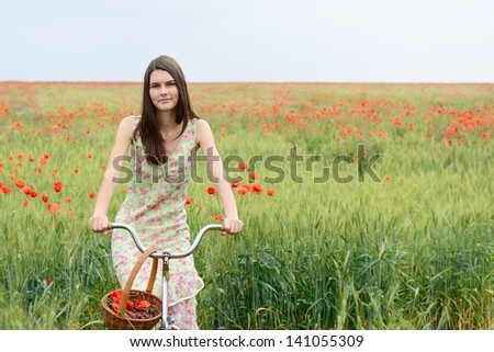 Young beautiful woman with bicycle and basket with cherry on a poppy field, summer outdoor. - stock photo