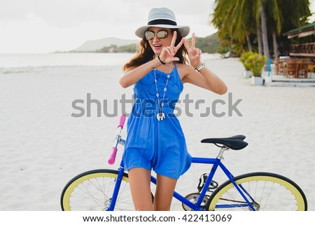 young beautiful woman with bicycle on beach, summer vacation, vintage style, bohemian outfit, blue dress, straw hat, sunglasses, smiling, happy, having fun, positive, showing peace signs with fingers - stock photo