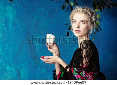Young beautiful woman with blond hair in braids romantic hairstyle enjoying cup of coffee against blue painted grunge wall with space for text - stock photo