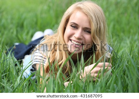 Young beautiful woman with blowball on green grass