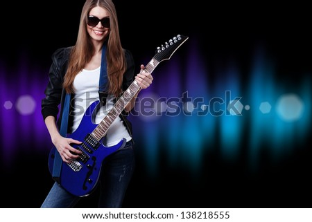 young beautiful woman with blue electric guitar wearing sunglasses - stock photo