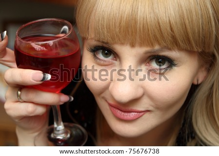 Young beautiful woman with bocal of red wine.