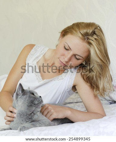 Young beautiful woman with british cat on the bed - stock photo