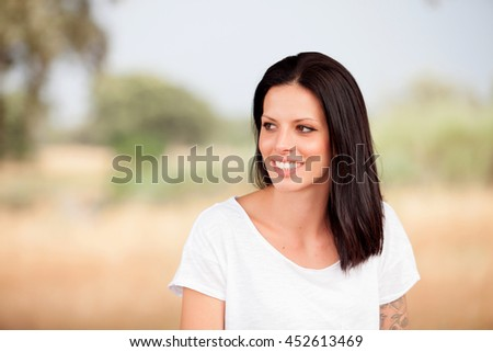 Young beautiful woman with brunette hair and perfect smile  posing in park  - stock photo