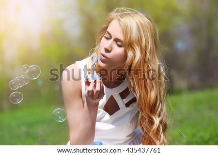 Young beautiful woman with bubbles on meadow