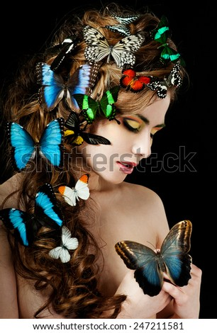 Young  beautiful woman with butterflies in her hair - stock photo