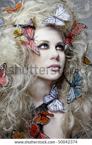 Young beautiful woman with butterfly in curly hair.