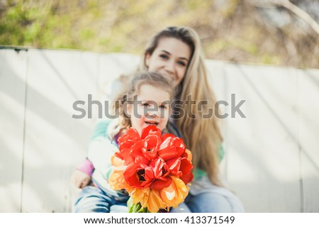 Young beautiful woman with child on the background laugh and smile sitting on the white wood bench  - stock photo