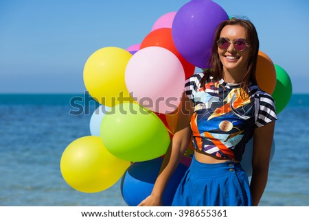 Young beautiful woman with colorful balloons on the beach. Summer vacation