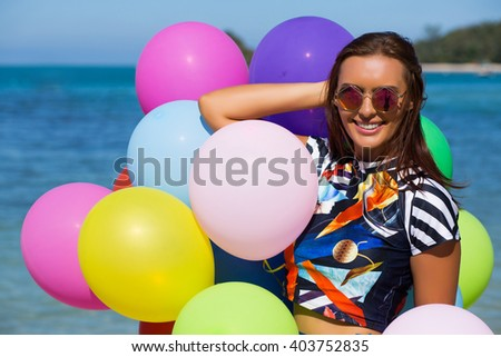 Young beautiful woman with colorful balloons on the beach. Summer vacations.