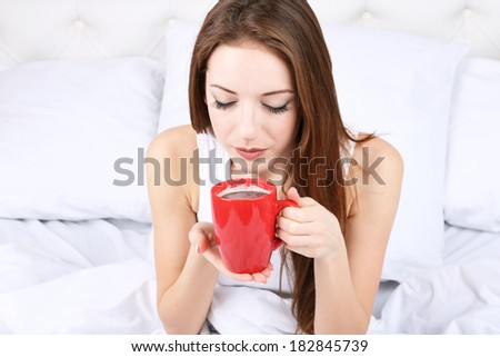 Young beautiful woman with cup of coffee in bed close-up - stock photo