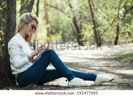 young beautiful woman with digital tablet sitting  in park - stock photo
