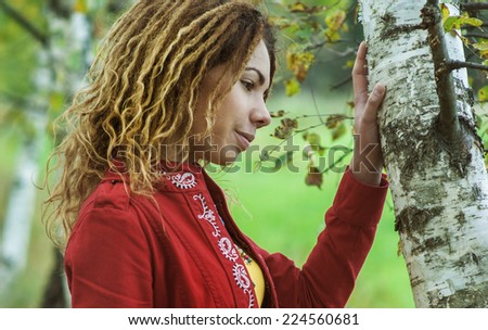 Young beautiful woman with dreadlocks in red clothes near birch. - stock photo