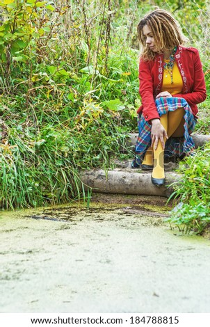 Young beautiful woman with dreadlocks in red clothes sits near marshes. - stock photo