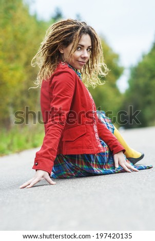Young beautiful woman with dreadlocks in red clothes sitting on pavement and laughs. - stock photo
