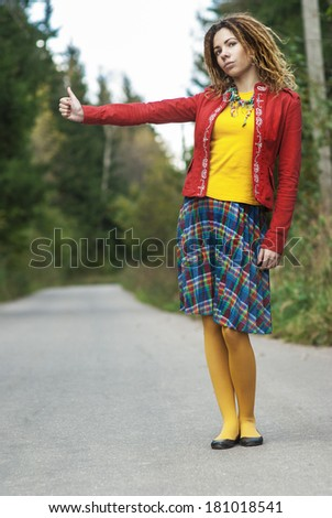 Young beautiful woman with dreadlocks in red clothes votes hitchhiking. - stock photo