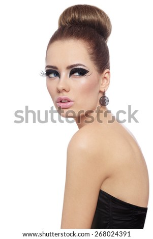 Young beautiful woman with fancy cat eye make-up and stylish hair bun over white background - stock photo