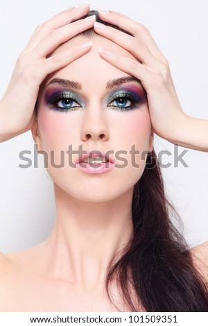 Young beautiful woman with fancy colorful make-up - stock photo