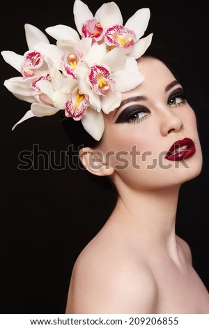 Young beautiful woman with fancy make-up and white orchids in her hair - stock photo
