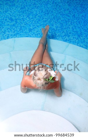 Young beautiful woman with flower in jacuzzi - stock photo