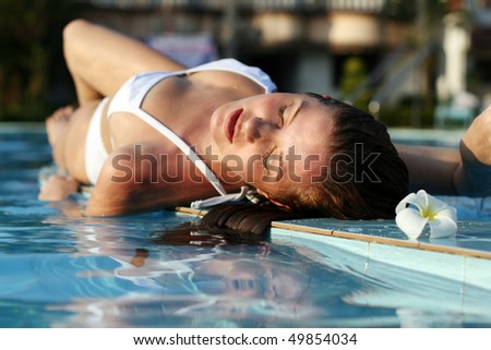young beautiful woman with flower in swimming pool - stock photo