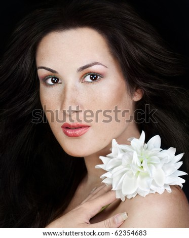Young beautiful woman with frackles holding flower in her hands - stock photo