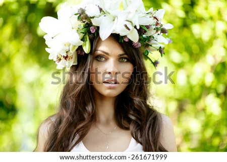 Young beautiful woman with freckles and dark hair in wreath of flowers outdoors in nature. - stock photo