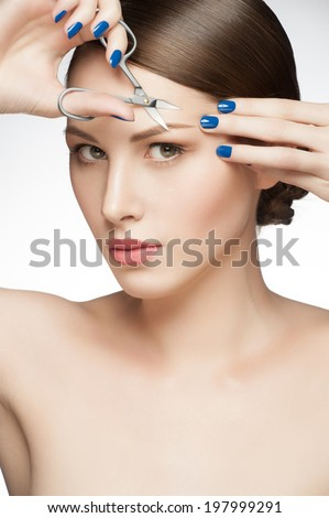 Young beautiful woman with fresh makeup cut her eyebrows, healthcare and beauty concept - stock photo