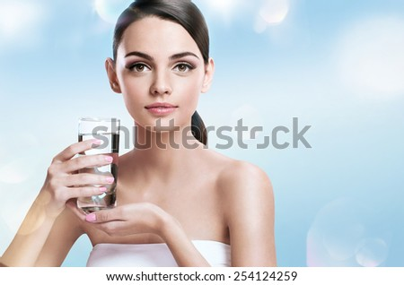 Young beautiful woman with glass of clear water, healthy life concept / photoset of the European appearance girl holing a transparent glass of water - isolated on white background   - stock photo