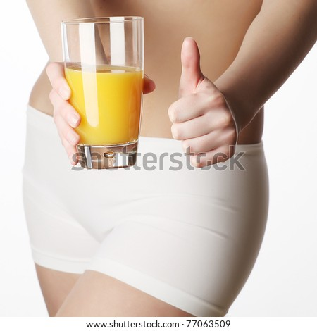 Young beautiful woman with glass of orange juice - stock photo