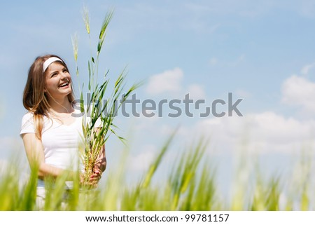 young beautiful woman with green wheat on sky background